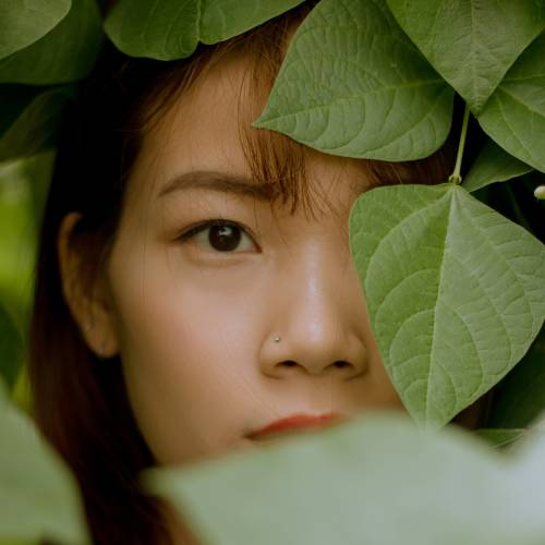 womans-face-on-green-leaves